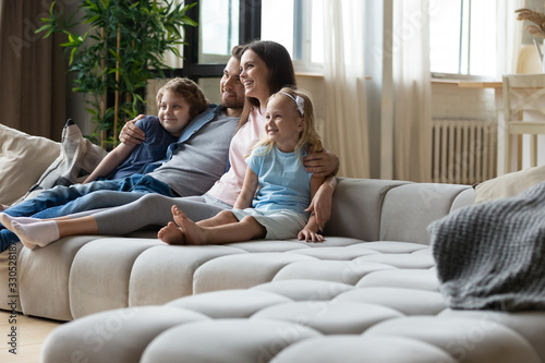 obraz PCV Happy young family with small kids sit relax on comfortable couch in living room watching movie together, smiling parents with daughter and son rest on cozy sofa enjoying weekend at home