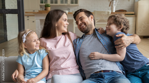 Overjoyed young parents with little preschooler daughter and son sit relax on co Wallpaper Mural