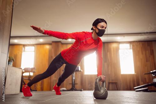 obraz PCV Sport Girl In Mask from Coronavirus doing Kettlebells Planking.