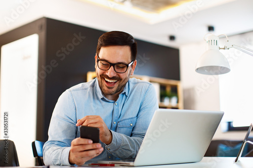Obraz Young business man working at home with laptop and uses a smartphone - fototapety do salonu
