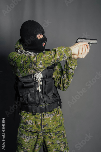 Fotografie, Tablou A man in camouflage uniform, body armor and a balaclava, holds his weapon ready and takes aim with a pistol, standing against a gray background