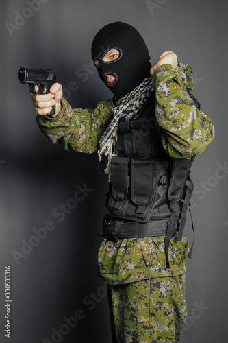 Obraz na plátne A man in camouflage uniform, body armor and a balaclava, holds his weapon ready and takes aim with a pistol, standing against a gray background