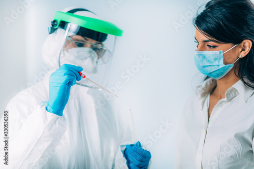 Obraz Coronavirus test. Medical worker in protective suite taking a swab for corona virus test, potentially infected young woman - fototapety do salonu