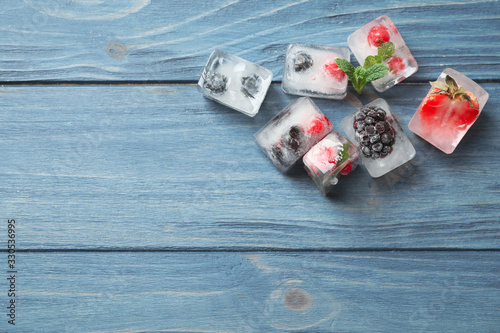Obraz Ice cubes with different berries and mint on blue wooden table, flat lay. Space for text - fototapety do salonu