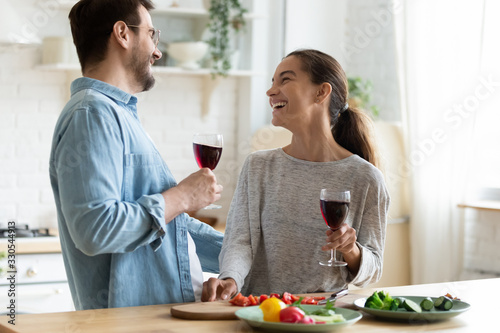 Obraz Young loving couple having fun in kitchen, drinking red wine, holding glasses, laughing beautiful wife and husband chatting, preparing salad, cooking dinner, enjoying free time together - fototapety do salonu