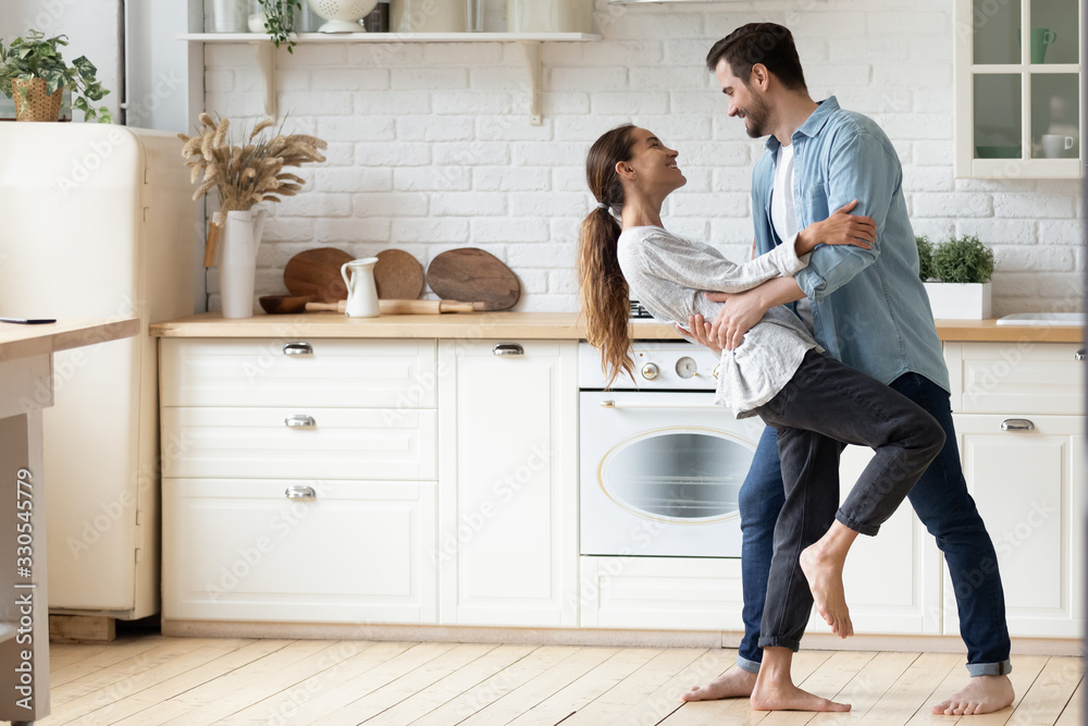 Fototapeta Happy loving young couple dancing romantic dance on date in modern kitchen, smiling husband and wife celebrating anniversary, enjoying tender moment, having fun, moving to music at home