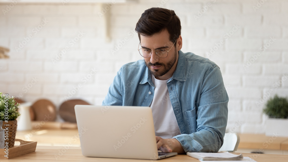 Fototapeta Serious man wearing glasses working on laptop online, sitting at table in kitchen, looking at computer screen, focused male using internet banking service, writing email, searching information