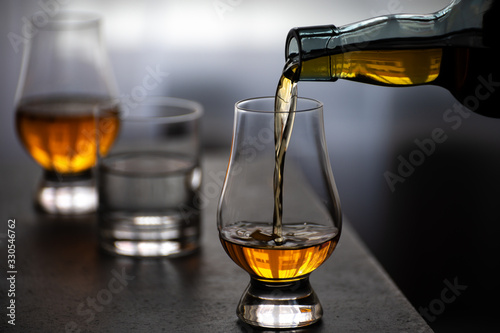 Obraz Pouring in tulip-shaped tasting glass Scotch single malt or blended whisky - fototapety do salonu