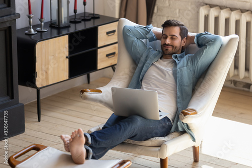 Fototapeta Calm young man relaxing with laptop on cozy armchair, peaceful male with closed eyes and hands behind head distracted from online work, enjoying lazy leisure time, daydreaming during break at home obraz