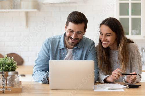 Obraz Happy young couple planning budget, reading good news in email, refund or mortgage approval, smiling woman and man looking at laptop screen, checking finances, sitting at table at home together - fototapety do salonu