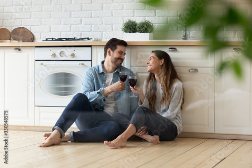 Obraz Happy loving couple clinking red wine glasses in modern kitchen, sitting on warm wooden floor together, smiling wife and husband celebrating relocation or anniversary, having fun, romantic date - fototapety do salonu