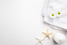 Spa Wellness Flat Lay. Spa Towel With Flowers, Candle And Seastares Over White Background, Top View. Beauty Set On The White Table.
