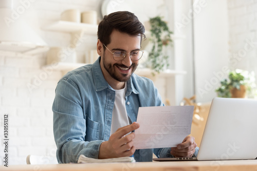 obraz PCV Smiling young man reading good news in paper notification, sitting at table with laptop, happy satisfied male wearing glasses holding document, job promotion, loan approval, great exam result
