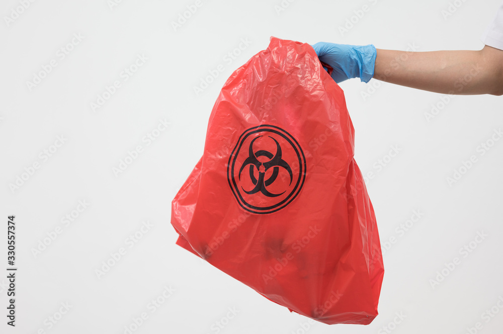 Fototapeta Scientist wearing blue gloves and red bag with bioharzard sign.A woman worker hand holding red garbage bag.Maid and infection waste bin at the indoor public building.Infectious control.