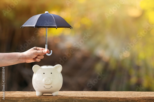 Leinwand Poster Piggy bank and woman hand hold the black umbrella for protect on sunlight in the public park, to prevent for asset and saving money for buy health insurance concept