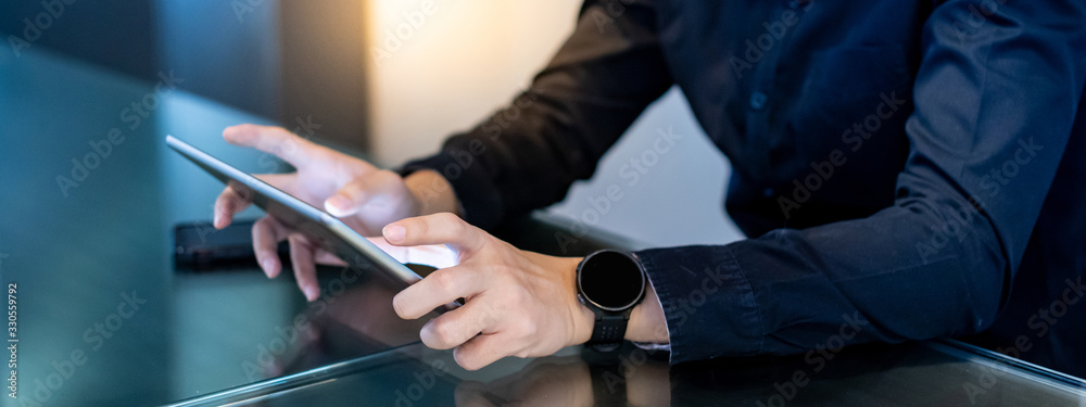 Fototapeta Businessman hand using digital tablet in office meeting room. Male entrepreneur reading news on social media app. Online marketing and Big data technology for E-commerce business.  - obraz na płótnie