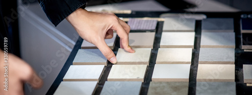 Obraz Male architect or interior designer hand choosing ceramic texture sample from swatch board in design studio. Floor and wall finishing material for architecture and construction industry. - fototapety do salonu