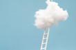 Leinwandbild Motiv ladder leading up to a puffy cotton cloud on a blue background.