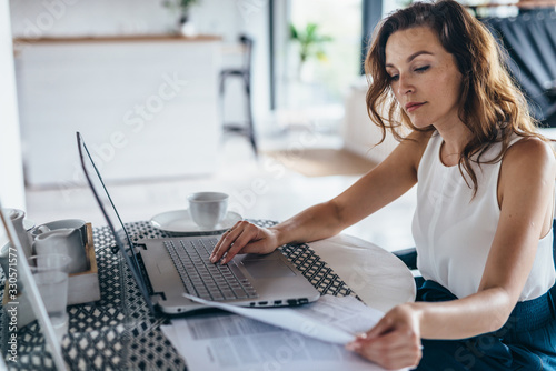 Photo Woman using laptop while sitting at table