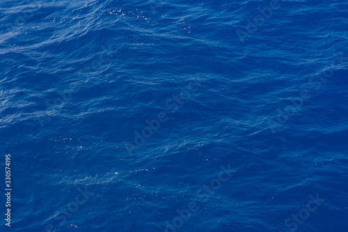 Clean pure Mediterranean sea surface with a lot of tiny waves, bubbles and foam. Copy space background.