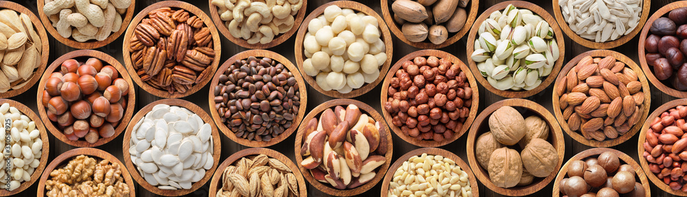 Fototapeta assorted nuts background, vegetarian food in wooden bowls, top view
