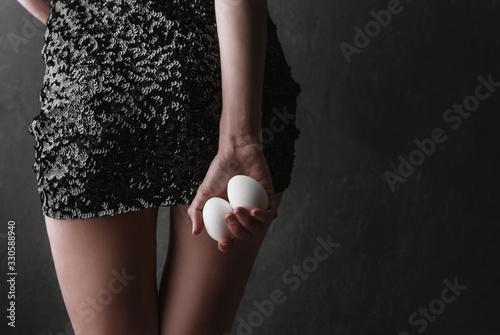 two chicken eggs in a female hand on a background of a black dress in sequins. concept of woman?s ability to control a man and his desires