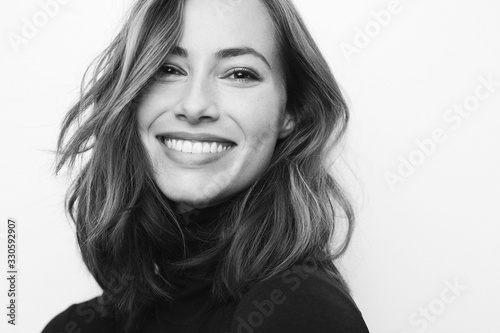 Billede på lærred Black and white portrait of young happy woman with a big smile on her face