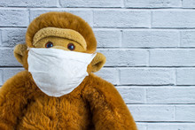 Toy Plush Monkey In A Homemade Medical Mask On The Background Of A Brick Wall With Space For Copying. Concept - Protection From Coronavirus.