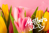 Holiday card - a bouquet of fresh spring pink and yellow tulips, holiday greetings, handwritten inscription with a brush Mothers Day, greeting lettering.