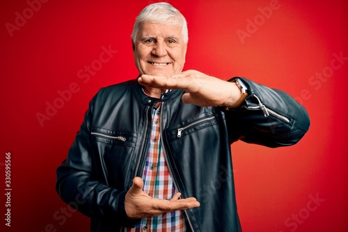 Fototapeta Senior handsome hoary man wearing casual shirt and jacket over isolated red background gesturing with hands showing big and large size sign, measure symbol. Smiling looking at the camera. Measuring obraz