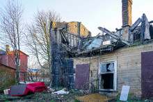 Old Wooden House After The Fire, Red Sofas Near The House