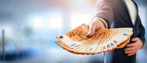 Fototapeta Business Man give a spread of euros cash over bank background. Euro currency detail. Money Banknotes banner. obraz