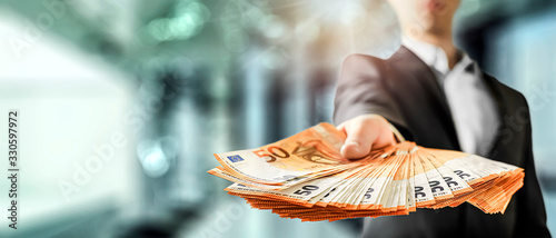 Business Man give a spread of euros cash over bank background. Euro currency detail. Money Banknotes wide banner or panorama.