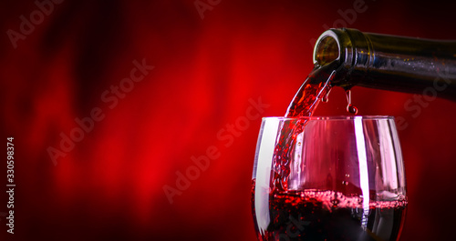 Leinwand Poster Pouring red wine into the glass against rustic background.