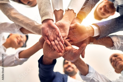 Group of business workers standing with hands together at the office Canvas Print