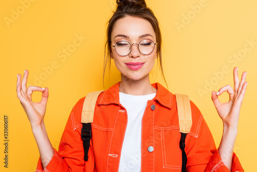 smiling student in eyeglasses standing in meditation pose with closed eyes isolated on yellow