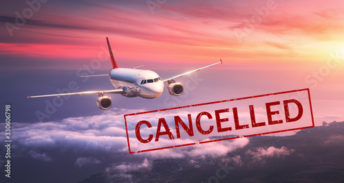 Obraz Airplane and flight cancellation. Canceled flights in Europe, Asia and USA airports. Travel cancelled because of pandemic of coronavirus. Background of flying passenger aircraft with text. Covid-19 - fototapety do salonu
