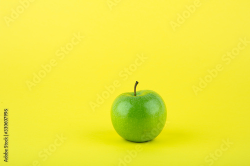 green apple on yellow background with copy space