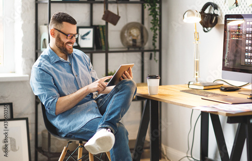 Obraz Young man using tablet at workplace. - fototapety do salonu