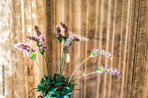 Purple lavender flowers bouquet arrangement inside vase potted plant closeup against window curtain blinds with fake cloth green leaves