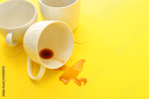 Fotografering Empty cups and spilled coffee on color background