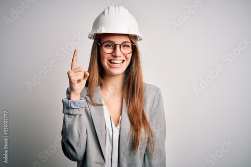Fototapeta Young beautiful redhead architect woman wearing security helmet over white background pointing finger up with successful idea. Exited and happy. Number one. obraz