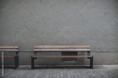 Closeup shot of wooden benches against a grey stone wall in an empty street