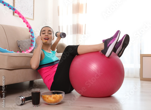 Fotografie, Tablou Lazy young woman with sport equipment eating junk food at home