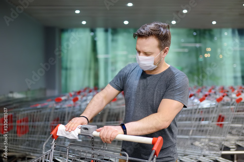 Fotografiet Man wearing disposable medical face mask wipes the shopping cart handle with a disinfecting cloth in supermarket