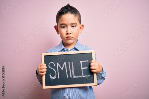 Fototapeta Young little boy kid showing blackboard with smile word as happy message over pink background with a confident expression on smart face thinking serious obraz