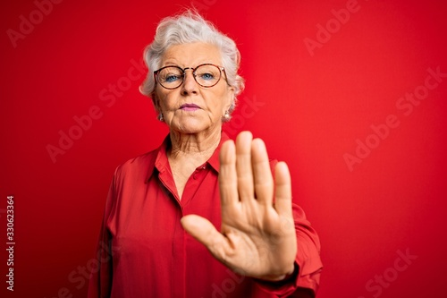 Obraz Senior beautiful grey-haired woman wearing casual shirt and glasses over red background doing stop sing with palm of the hand. Warning expression with negative and serious gesture on the face. - fototapety do salonu
