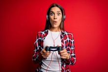 Young Beautiful Brunette Gamer Woman Playing Video Game Using Joystick And Headphones Scared In Shock With A Surprise Face, Afraid And Excited With Fear Expression