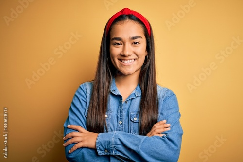 Fototapeta Young beautiful asian woman wearing casual denim shirt and diadem over yellow background happy face smiling with crossed arms looking at the camera. Positive person. obraz