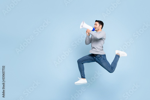 Young active man jumping and shouting on megaphone isolated on light blue backgr Canvas Print